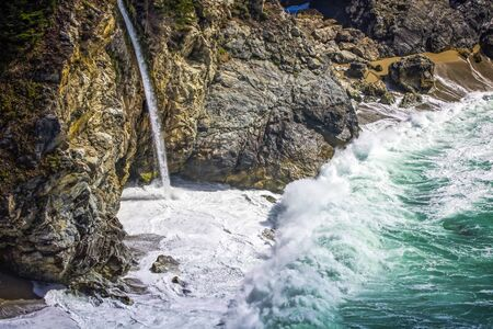 McWay Falls pours onto beach with high surf breaking on California Highway 1 near Big Sur.