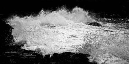 Foam and formations in surging surf in black and white image.