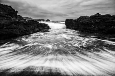 Black and white dramatic seascape with water in motion against rocky shore.