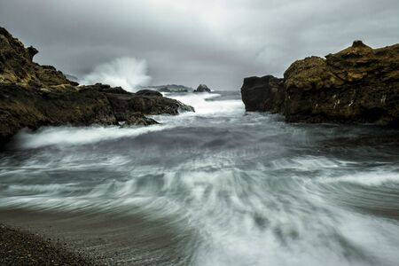 Dramatic California stormy seascape with water in motion and spray from surf striking rocky shore. 版權商用圖片