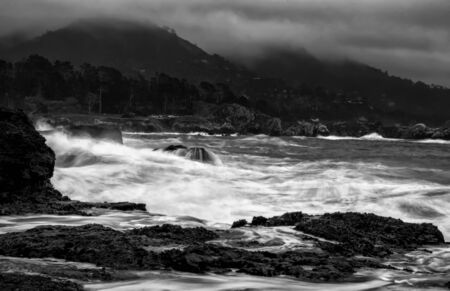Black and white California coastal seascape with surging waves, cloudy skies, rocky coast and mountains.