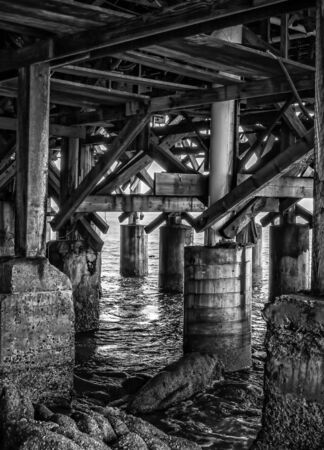 Black and white pier pilings and ocean water with coast taken underneath pier in California.