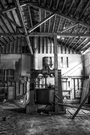 Old equipment sits in abandoned cannery in Monterey, California.  Black and white dramatic grunge in historic building. Stock Photo