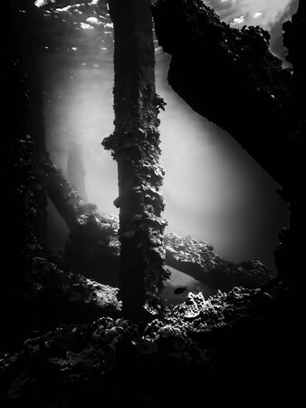 Dramatic abstract black and white underwater image of collapsed pier.