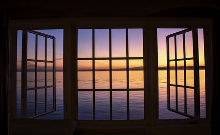 Dawn over the ocean in sunrise colors taken through black window frame in California.