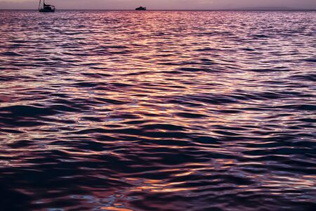 Sunset light glows on calm ocean surface in bright colors of pink and purple.