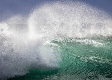 Big breaking wave with glowing green water and big white spray and foam filling the frame.  Image taken in Hawaii.