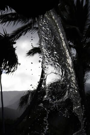 Conceptual look through pouring water with mountains and palm trees in Hawaii.