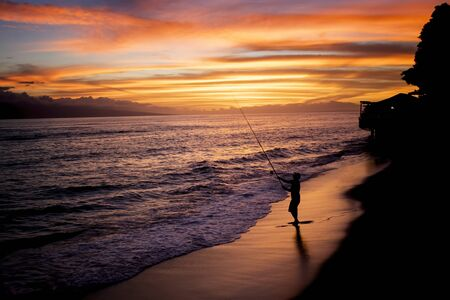 Man in silhouette fishes as the sun sets below the horizon on tropical island.