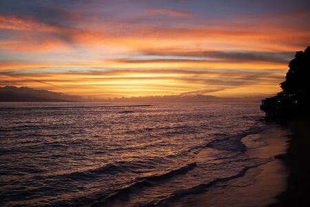 Sunset over the ocean with bright colors of orange and purple reflecting on surface of sea.