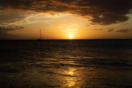 Sunset seascape with boat on horizon under orange sky reflecting on surface of Pacific. Imagens