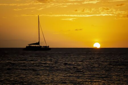 Silhouettes of people watching sun setting below the horizon from the deck of a boat.  Orange sky and ocean fill frame.