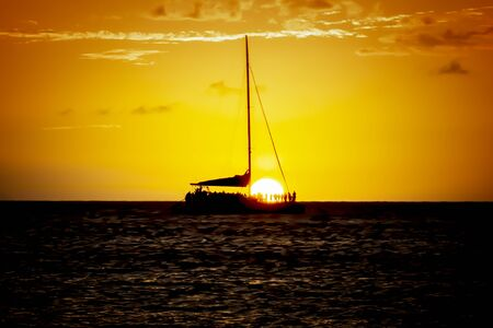 Sunset sail with sun dropping below the horizing and row of people in silhouette watching from boat. Imagens
