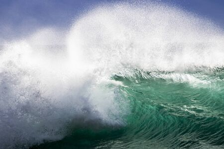 Powerful close up breaking green wave with white spray in Hawaii. Imagens