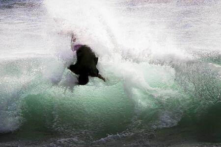 Man upside down in green wave skimboarding in the surf in Hawaii.