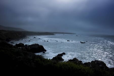 Moody foggy early morning on California coast with foamy surf and dark rocks under cloudy blue gray sky.