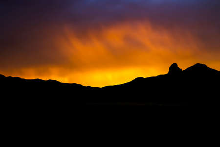 Vivid sunset through rain band and clouds over black mountain silhouette on horizon.  Desert sunset from Arizona.