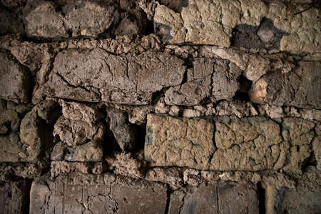 Detail of old adobe wall made of mud and straw bricks in colors of brown and black with rough texture.