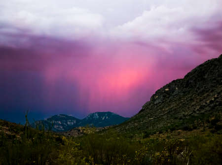 Rain bands under clouds blaze with pink light at sunset in an Arizona landscape.