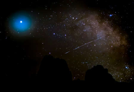 Milky Way with comet shooting through in desert night sky with mountain silhouette on horizon. Stock fotó