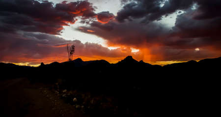 Sunset glows below horizon lighting rain bands and clouds vibrant orange with desert landscape spread out below.