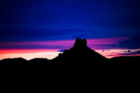 Sunset desert sky in vibrant color with mountain in black silhouette on horizon.