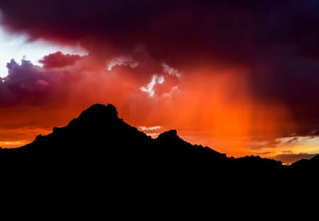 Vibrant purple and orange rain bands at sunset under dark clouds with black mountains in silhouette on horizon.