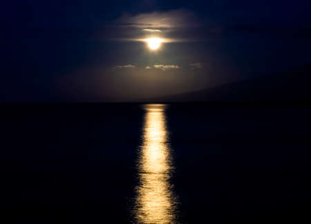 Full moon dropping through clouds and setting over ocean with light glowing on surface of the sea in Hawaii.