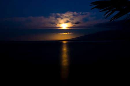 Full moon setting over ocean in early morning with golden orange light reflecting on ocean in tropical Hawaii.
