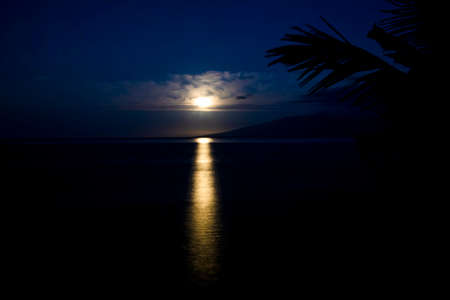 Full moon setting through clouds and reflecting on surface of the sea in tropical Hawaii.