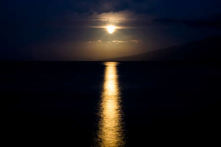 Full moon setting through clouds looks like it is dripping with light glowing on ocean surface.