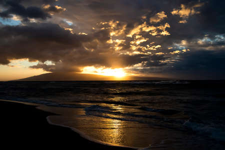 Sun setting behind island witih golden light glowing on ocean survace and water flowing onto beach. Stock fotó