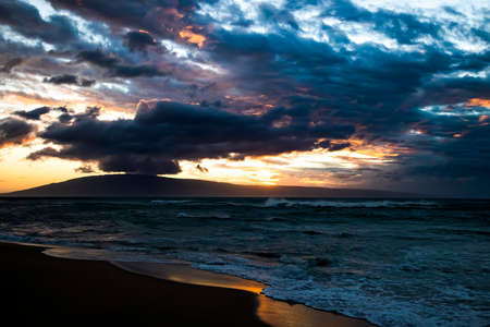 Dramatic clouds and sky over stormy sea at sunset with island on horizon.