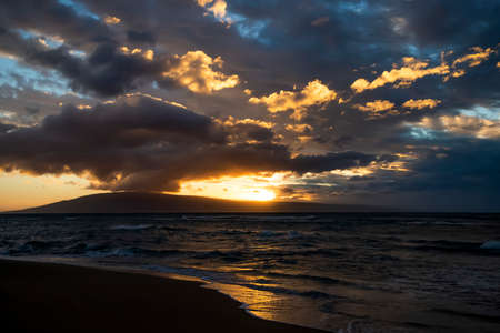 Sunset light glowing through clouds and reflecting on ocean surface with island on horizon. Stock fotó