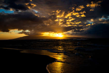 Golden sunset seascape with light rays beaming from beneath clouds as sun sets behind tropical island. Stock fotó