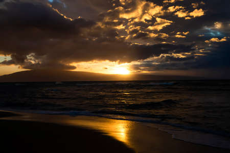 Sunset reflected in wet sand on beach in twilight seascape in Hawaii. Stock fotó