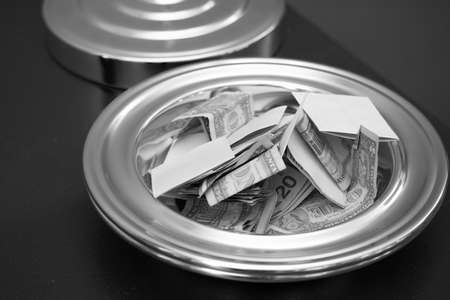 A tithe plate with money in it. Black and white.
