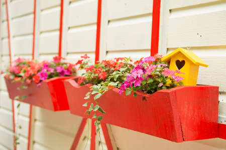 planters: Flowers and a yellow bird house in bright red planters mounted on the side of a white and red building.