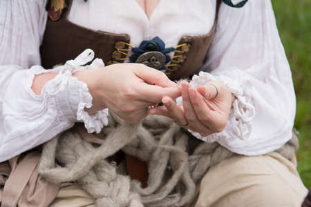 A woman spins wool by hand dressed in Renaissance costume.