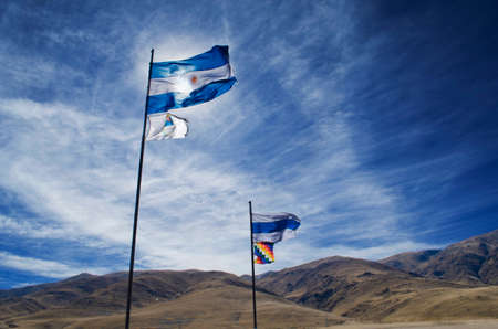 Argentine flag and flag of native peoples waving in the mountains