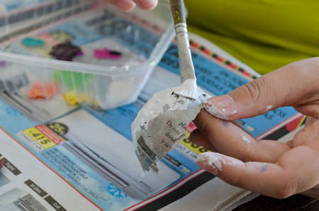 Een meisje dat met acrylverf een papieren masker schildert
