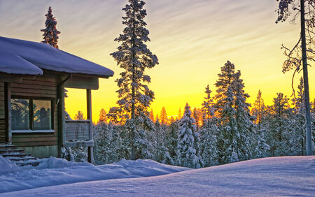 Wooden cottage house at winter sunset in Finland