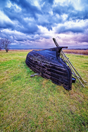 overthrown: Overthrown fisherman boat on the lake shore at stormy weather