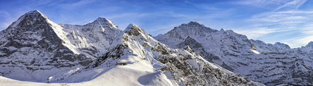 eiger: Panorama of four alpine peaks (Jungfrau, Eiger, Monch and Tschuggen) and skiing resort in swiss alps Stock Photo