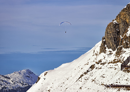 Paraglider in winter swiss alps photo