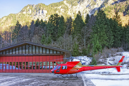 heliport: Red helicopter at swiss highland alpine heliport Editorial