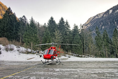 heliport: Red helicopter at swiss alpine heliport in winter Stock Photo