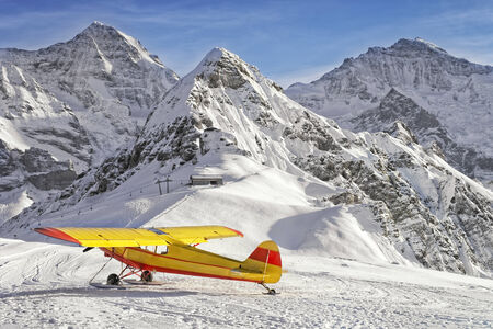 monch: Yellow red airplane at the mountain airfield in swiss alps in front of peaks Monch, Tschuggen and Jungfrau