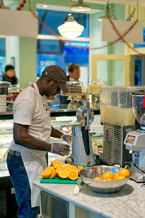 extracting: Black man extracting orange juice at cafe counter Stock Photo
