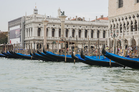doges  palace: Row of gondolas near Doges palace in summer Venice, St. Marco lion statue in summer Venice